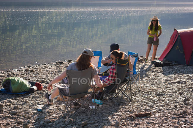 Group of hikers camping near riverside at countryside — Stock Photo