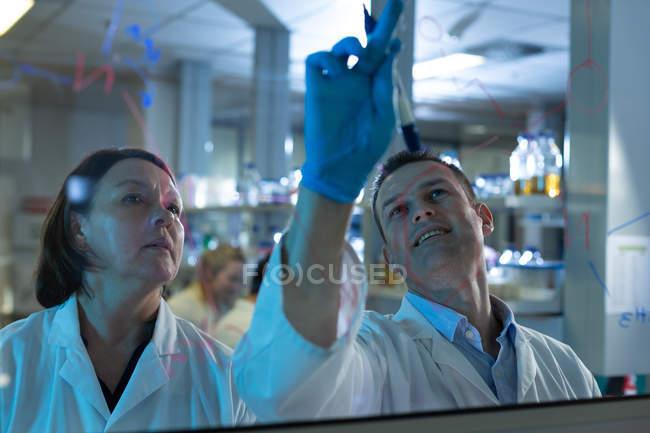Equipe de cientista discutindo na placa de vidro em laboratório — Fotografia de Stock