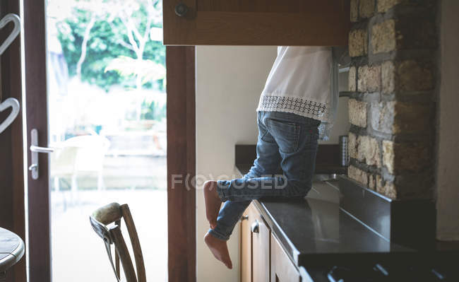 Low section of girl searching for food in kitchen at home — Stock Photo