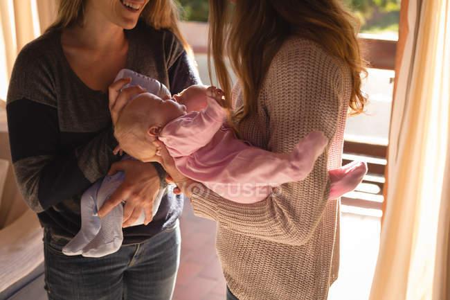 Metà di sezione di coppia lesbica che tengono i loro bambini a casa — Foto stock