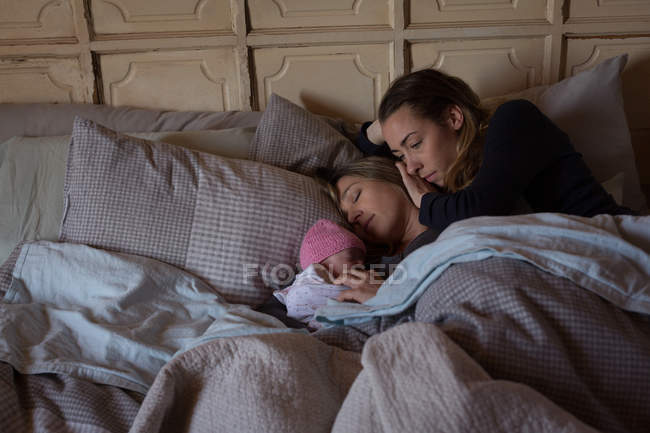 Lesbian couple with baby relaxing on bed at home — Stock Photo