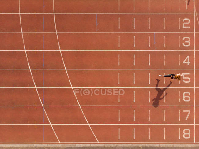 Young female athletic running on sports track — Stock Photo