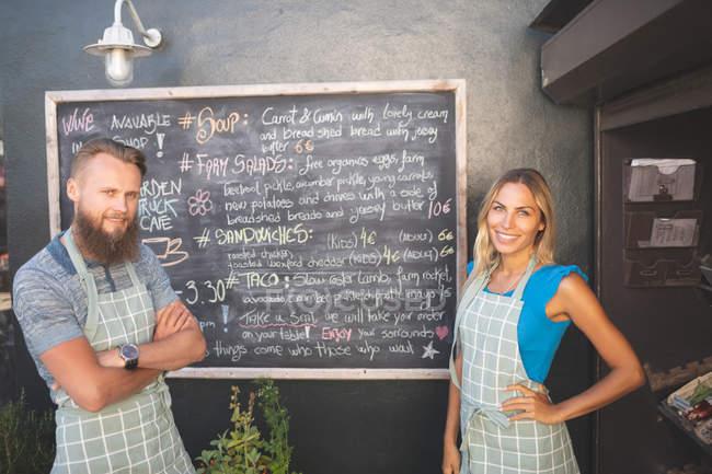 Портрет подружжя стоїть біля борту меню в харчової вантажівка — стокове фото