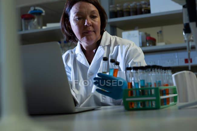Scienziato femminile che esamina la provetta in laboratorio — Foto stock