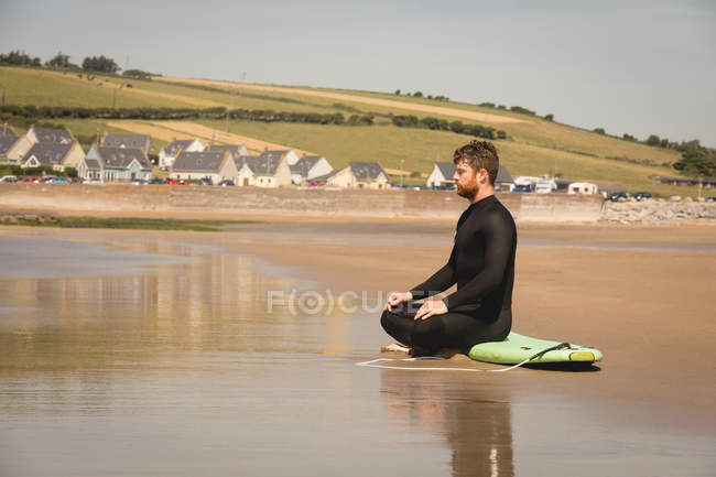 Surfer sitting on surfboard at beach on a sunny day — Stock Photo