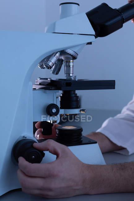Científico masculino usando microscopio en laboratorio - foto de stock