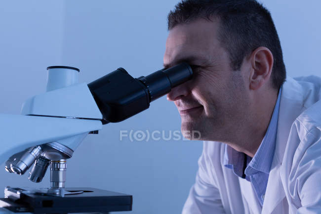 Male scientist using microscope in laboratory — Stock Photo