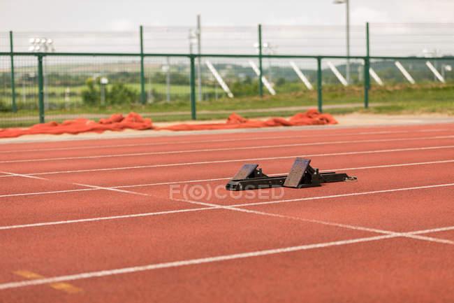 Стартовые блоки на беговой дорожке на спортивном объекте — стоковое фото