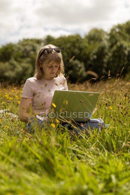 Young woman using laptop in the field — Stock Photo