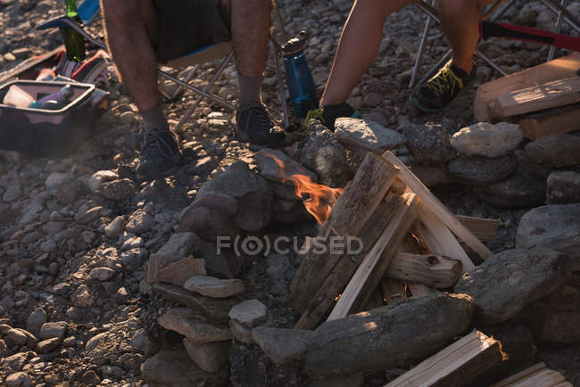 Low section of couple camping near campfire — Stock Photo