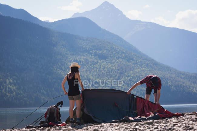 Couple en préparation pour mettre en place une tente sur une journée ensoleillée — Photo de stock