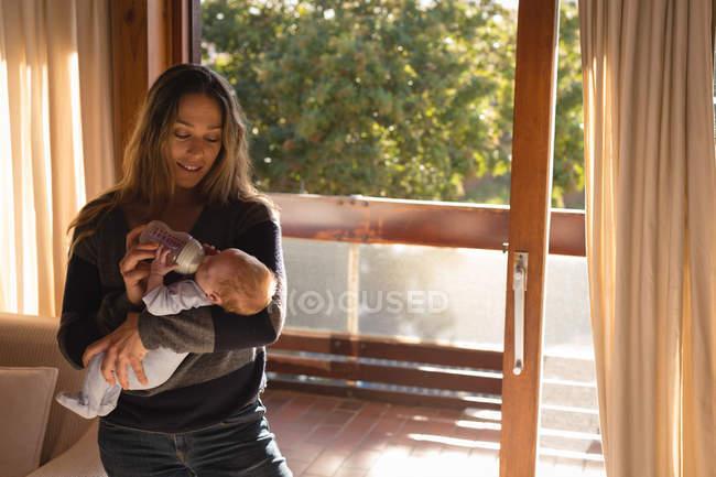 Mutter füttert ihr Baby zu Hause mit Milchflasche — Stockfoto