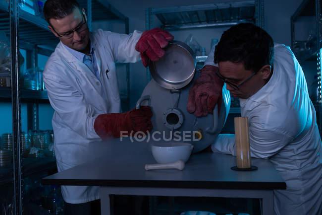 Männliche Wissenschaftler gießen im Labor Flüssigkeit in eine Schüssel — Stockfoto