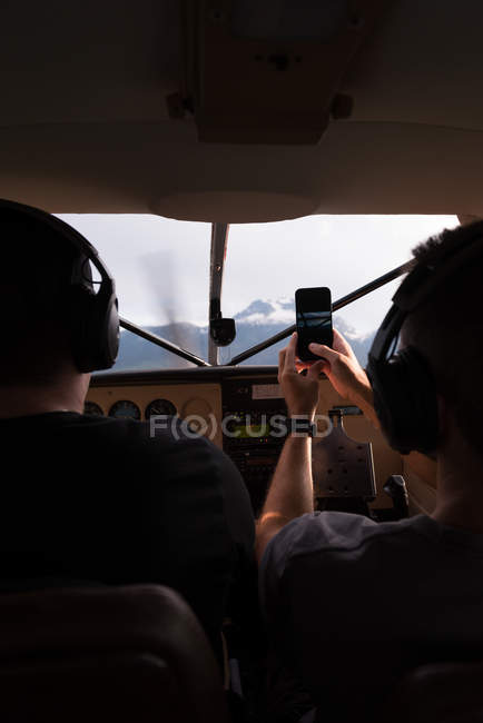Vue arrière du pilote avion volant tout en copilote prendre des photos avec téléphone portable — Photo de stock