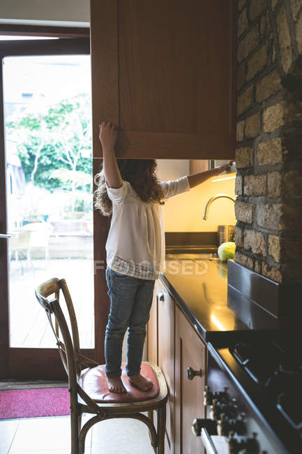 Girl searching for food in kitchen at home — Stock Photo