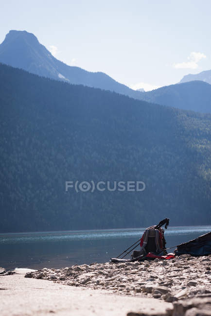Backpack and hiking pole near riverside on sunny day — Stock Photo