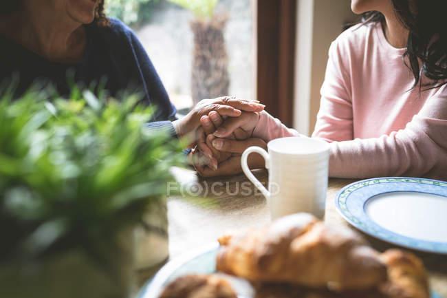 Средняя часть матери и дочери утешают друг друга дома — стоковое фото