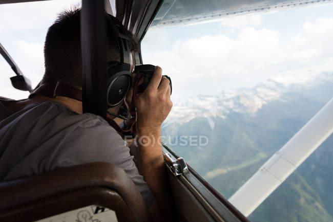 Pilote de prendre des photos avec l'appareil photo alors qu'il volait dans le cockpit de l'avion — Photo de stock
