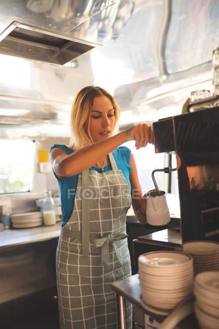 Красивая официантка готовит кофе в фургоне — стоковое фото