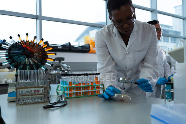 Female scientist using magnifying glass in laboratory — Stock Photo