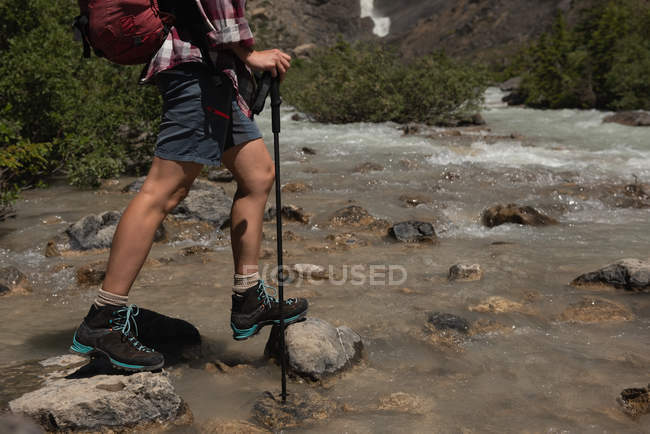 Low section of female hiker crossing the stream at countryside — Stock Photo