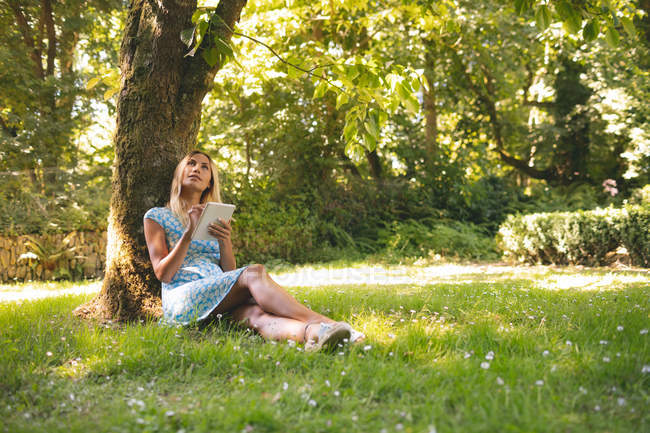 Young woman using digital tablet in the park — Stock Photo