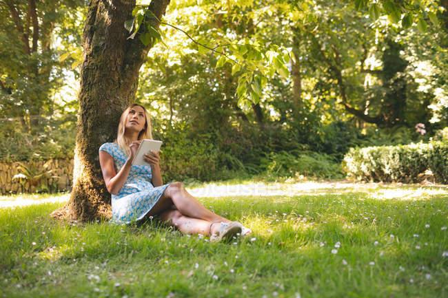 Mujer joven usando tableta digital en el parque - foto de stock