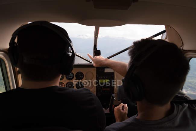 Pilotos hablando uno al otro durante el vuelo en cabina de avión - foto de stock