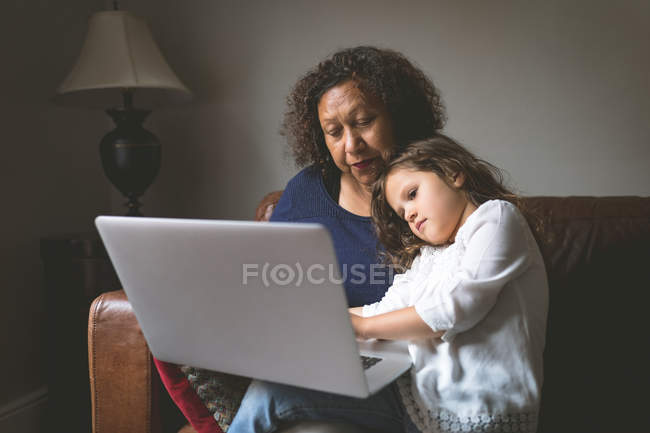 Little girl using laptop with grandmother on sofa at home — Stock Photo