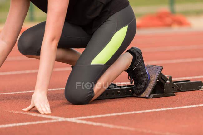 Низкая секция спортсменки готова к бегу по беговой дорожке — стоковое фото
