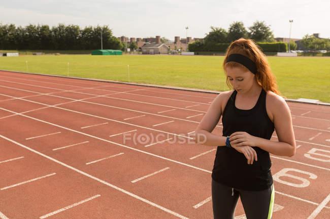 Jeune femelle athlétique à l'aide de smartwatch sur la piste de course — Photo de stock