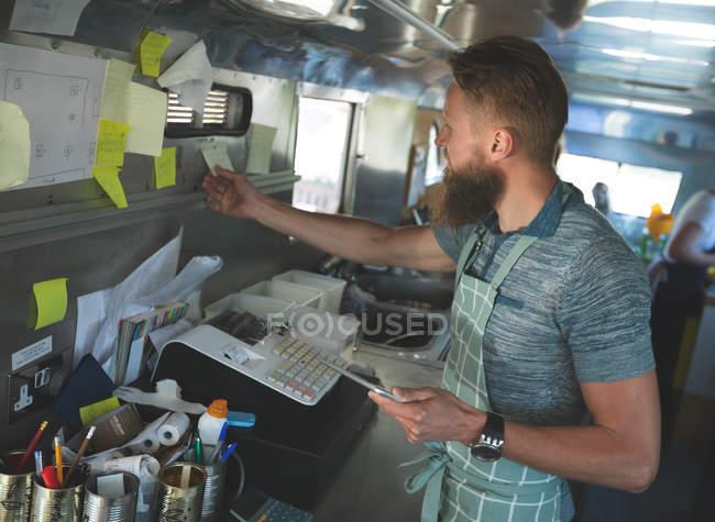 Camarero mirando órdenes de nota adhesiva en carro del alimento - foto de stock