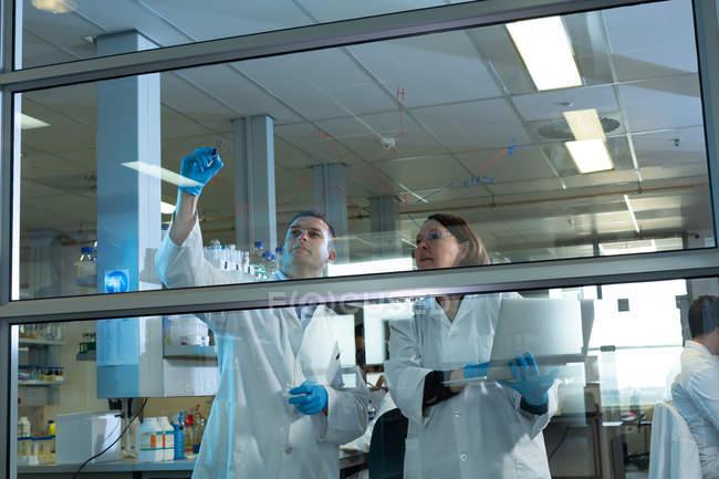 Wissenschaftlerteam diskutiert auf Glasplatte im Labor — Stockfoto