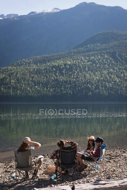 Group of hikers camping near riverside in mountains — Stock Photo