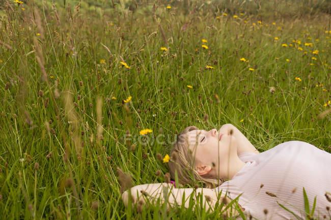 Молодая женщина отдыхает в поле — стоковое фото