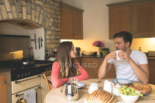 Пара взаємодіють один з одним в будинку маючи сніданок — стокове фото