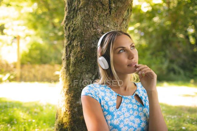Mulher atenciosa ouvindo música em fones de ouvido no parque — Fotografia de Stock