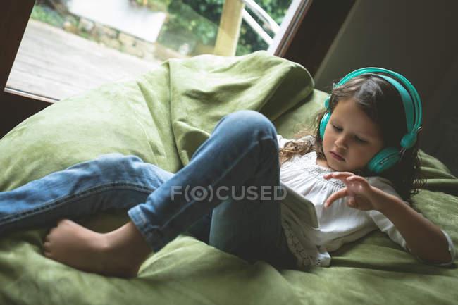 Mädchen hört zu Hause Musik mit digitalem Tablet — Stockfoto