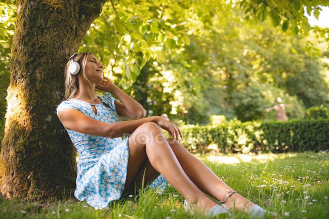 Femme écoutant de la musique contre un arbre dans le parc — Photo de stock