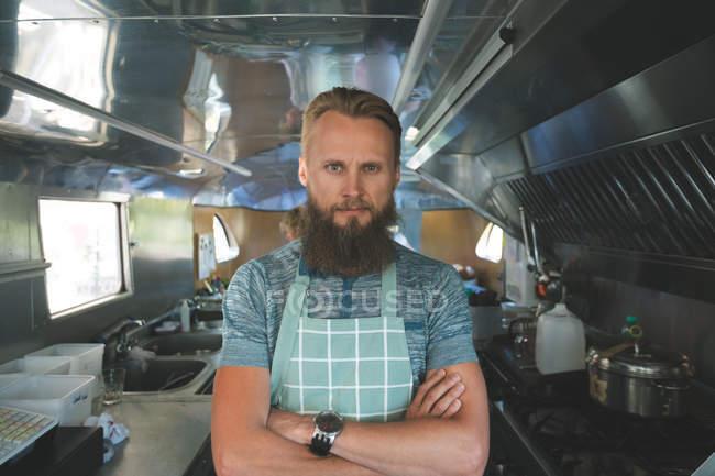 Офіціант з обіймами перетнула дивлячись на камеру в харчової вантажівка — стокове фото