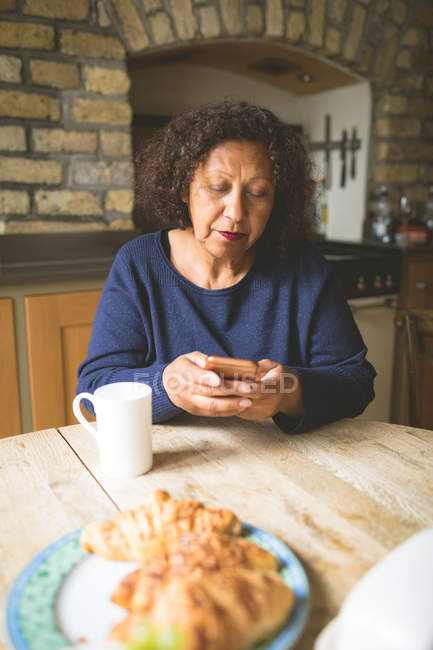 Senior woman using mobile phone in kitchen at home — Stock Photo