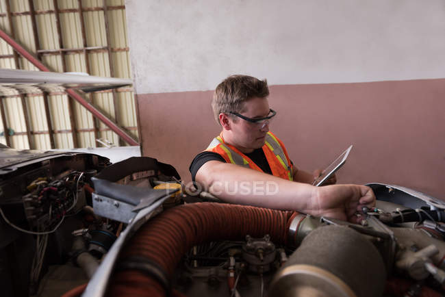 Mechanic using digital tablet while servicing aircraft engine at aerospace hangar — Stock Photo