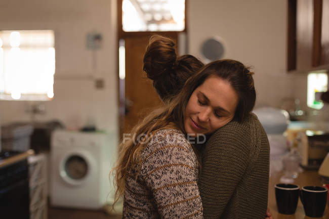 Lesbian couple hugging in kitchen at home — Stock Photo