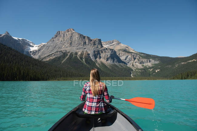 Rear view of woman boating in river in mountains — Stock Photo