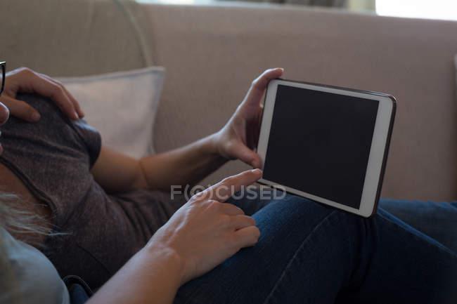 Крупным планом Лесбийская Пара с помощью цифрового планшета на диване у себя дома — стоковое фото