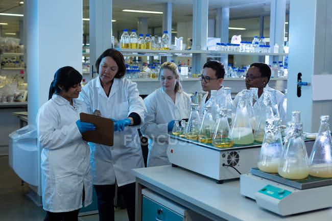Equipe de cientista interagindo sobre a área de transferência no laboratório — Fotografia de Stock