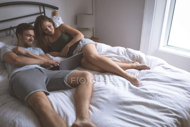 Casal usando laptop no quarto em casa — Fotografia de Stock