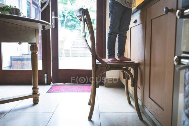 Section basse de fille debout sur la chaise dans la cuisine à la maison — Photo de stock