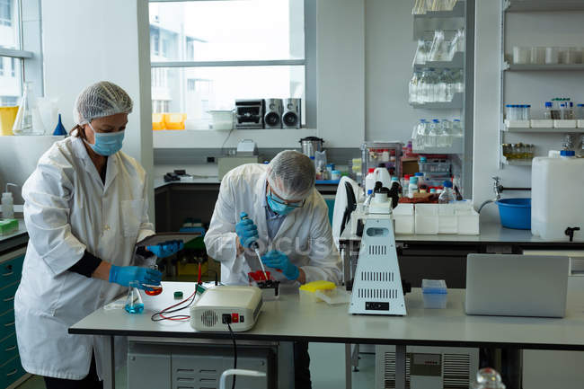 Scientists experimenting together in laboratory — Stock Photo