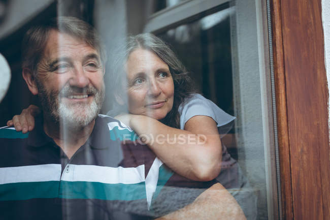 Happy senior couple looking through window at home — Stock Photo